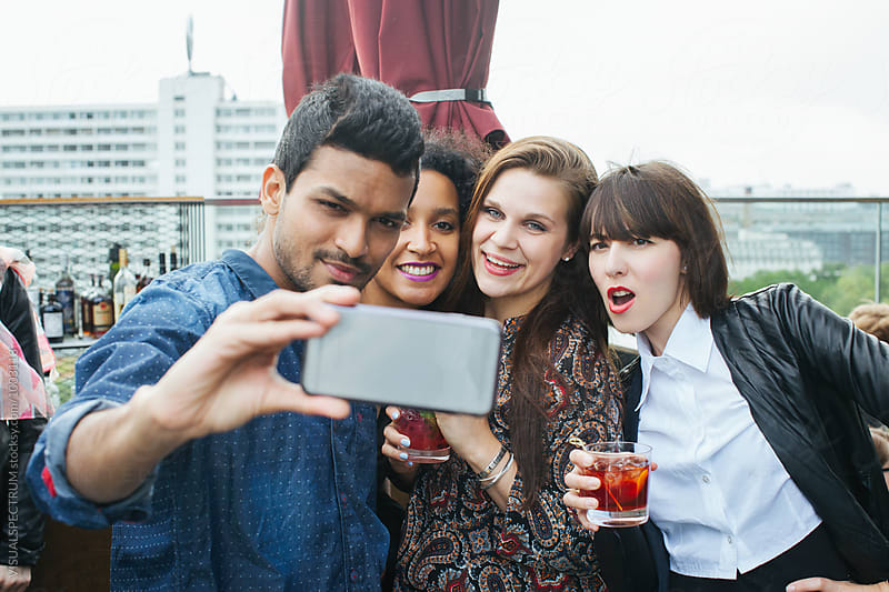 Cool Young Indian Man Taking Smartphone Selfie With Three Tipsy Young Women at Rooftop Bar by VISUALSPECTRUM for Stocksy United