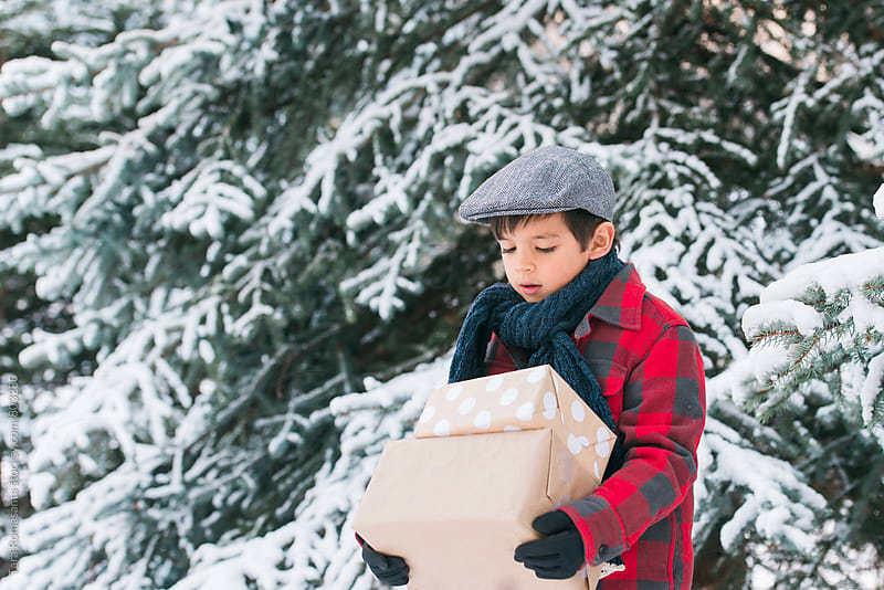 young boy carrying gifts outside in the snow by Tara Romasanta for Stocksy United