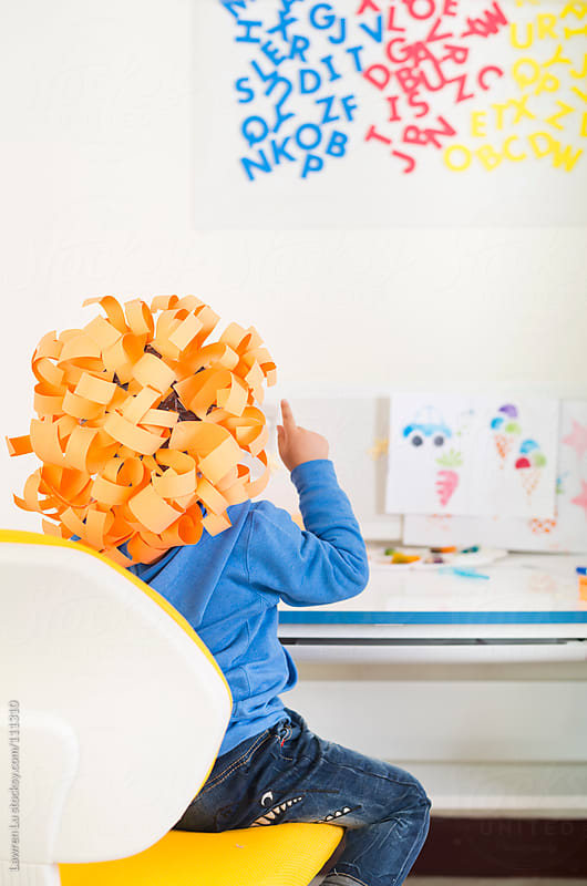 Kid wears funny crafts on head  and read alphabet on wall by Lawren Lu for Stocksy United