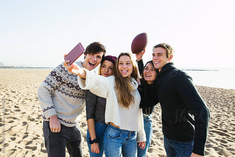 Group of teenage friends taking a selfie on the beach. by BONNINSTUDIO for Stocksy United