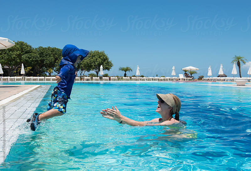 Little boy jumping into his mothers arms into a pool in Brazil by Emmanuel Hidalgo for Stocksy United
