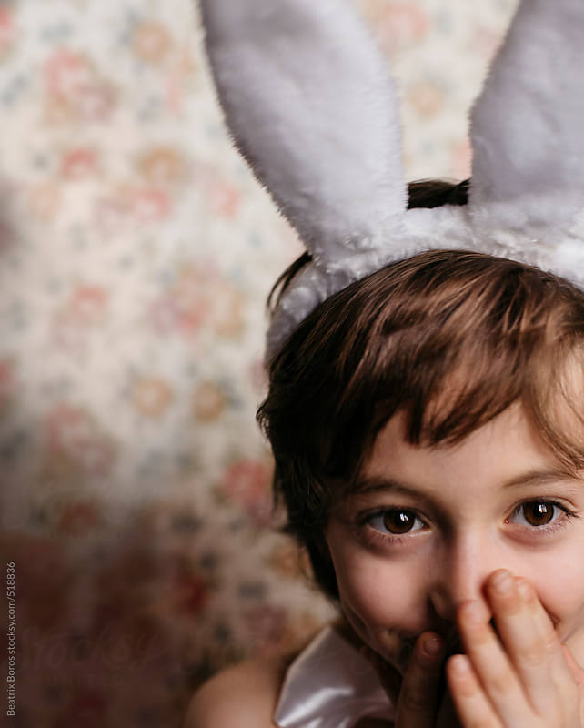 Child playfully smiling, wearing bunny ears, and hiding his mouth with his hands by Beatrix Boros for Stocksy United