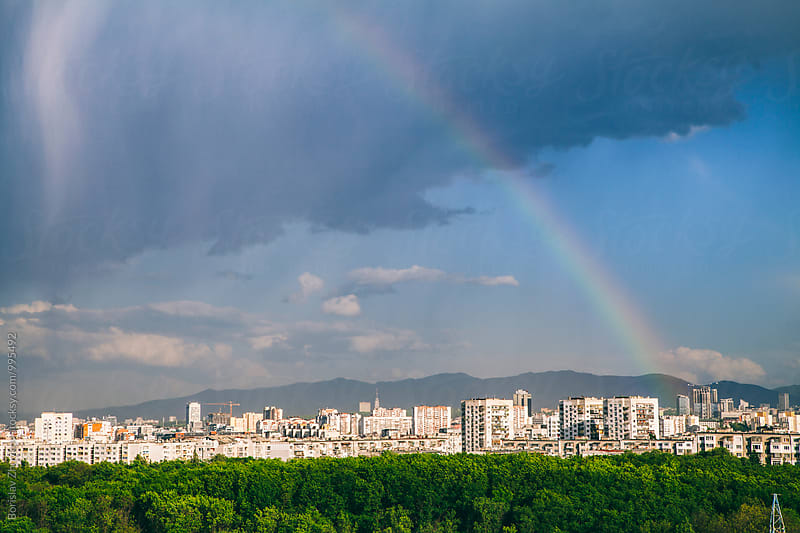 Rainbow above the cityscape by Borislav Zhuykov for Stocksy United