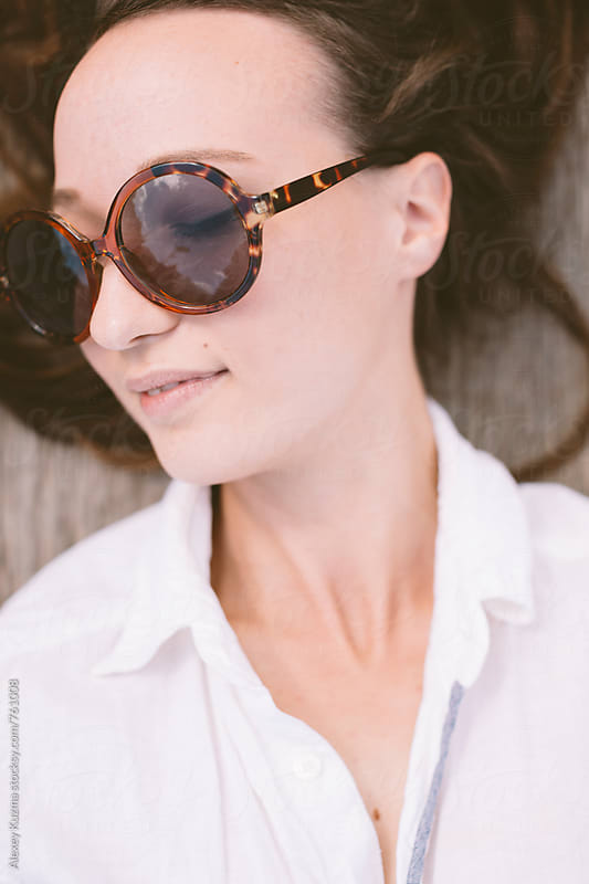 happy young woman with round sunglasses by Alexey Kuzma for Stocksy United