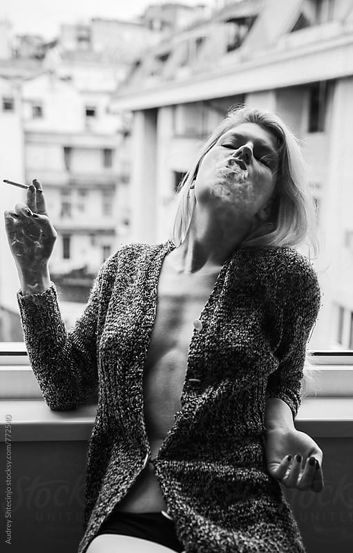 Portrait of sensual female on window smoking. by Marko Milanovic for Stocksy United