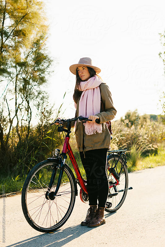 Woman with her bicycle on a forest road.  by BONNINSTUDIO for Stocksy United