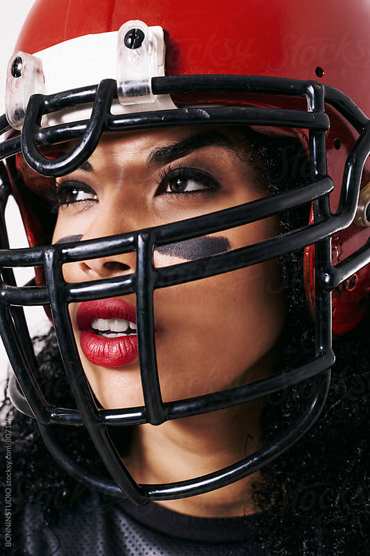 Portrait of a woman wearing a red football helmet. by BONNINSTUDIO for Stocksy United