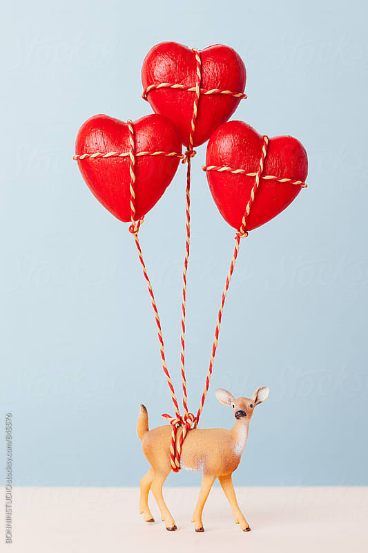 Deer toy holding red heart balloons. by BONNINSTUDIO for Stocksy United