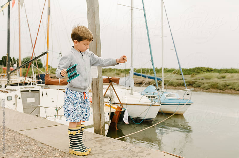 Young boy pulling up fishing line to check for crabs by Rebecca Spencer for Stocksy United