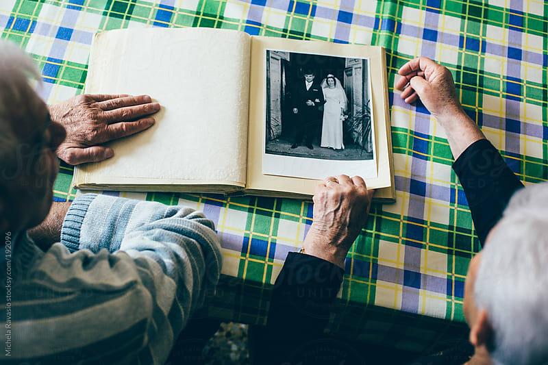 Elderly couple looking at their wedding album by michela ravasio for Stocksy United