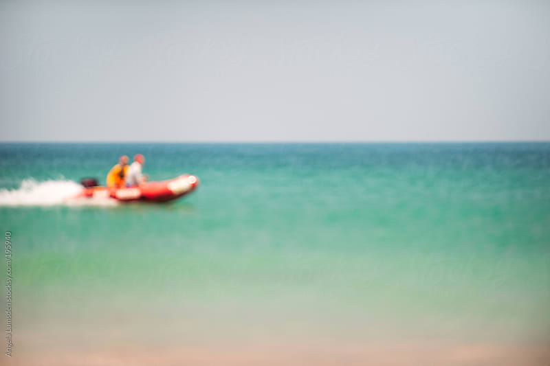 Blurred image of surf lifesavers in a rescue boat by Angela Lumsden for Stocksy United