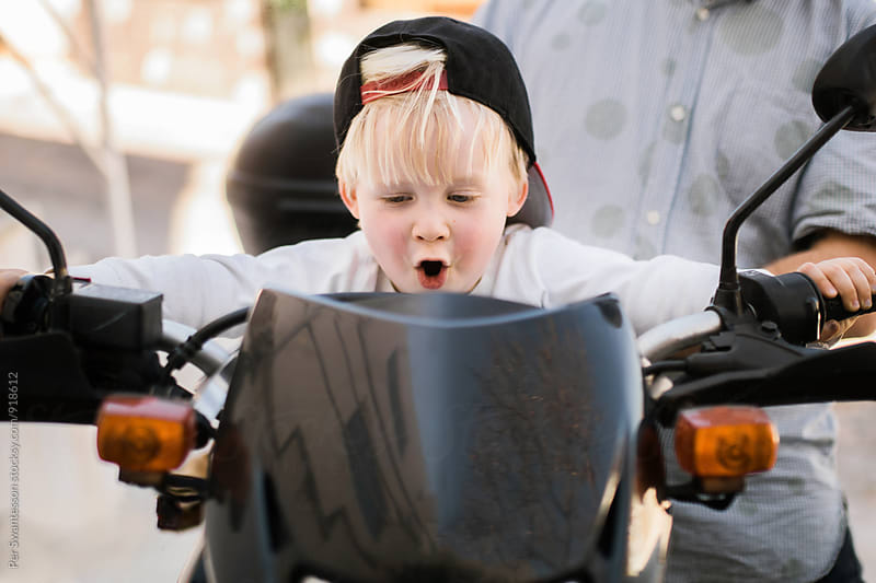 Excited toddler on motorbike by Per Swantesson for Stocksy United