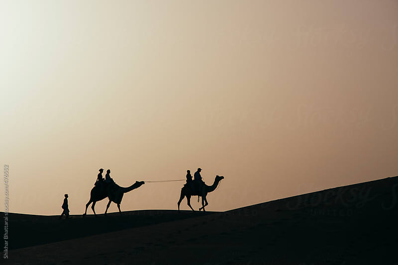 Silhouette of tourist enjoying a camel ride in the desert of Rajasthan, India. by Shikhar Bhattarai for Stocksy United