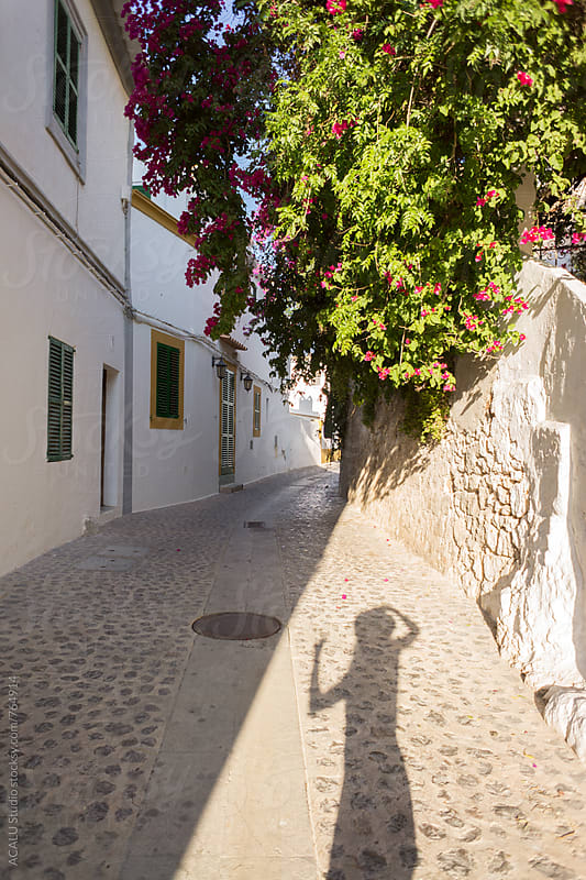 Shadow silhouette of a young tourist photographing a typical street in Ibiza, Spain by ACALU Studio for Stocksy United