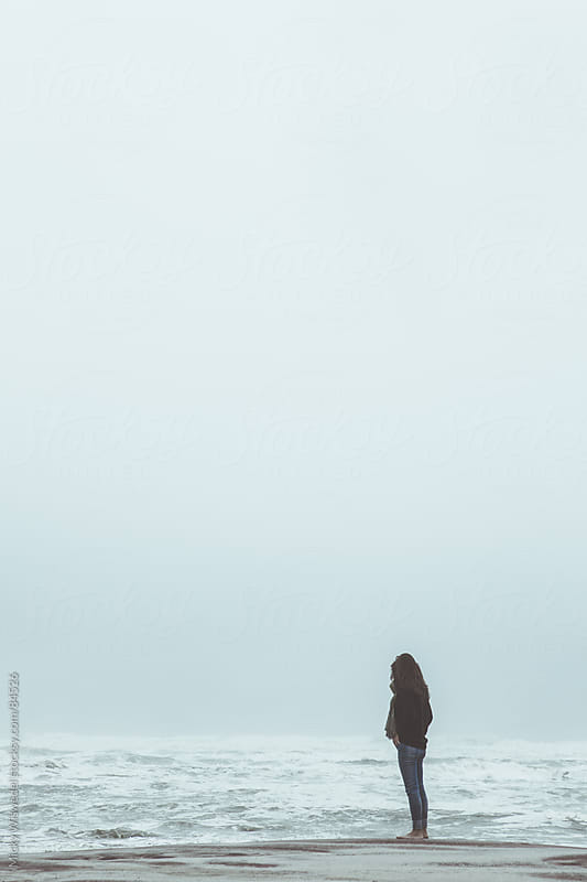 Woman standing on a misty beach by Micky Wiswedel for Stocksy United
