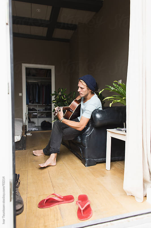 Young man sitting couch in his room, playing guitar, relaxing by Ivar Teunissen for Stocksy United