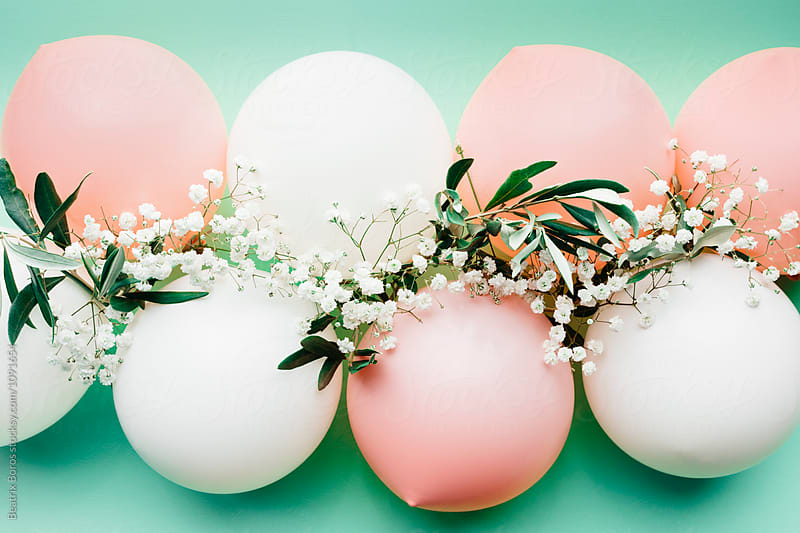 Pastel balloons with white floral decoration by Beatrix Boros for Stocksy United