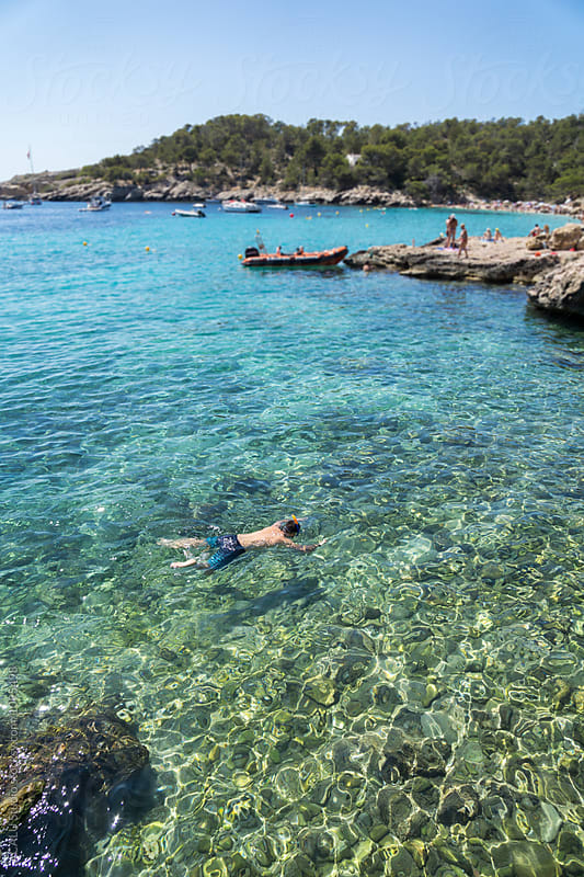Man snorkeling in clear waters at mediterranean sea by ACALU Studio for Stocksy United
