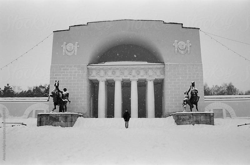 A black and white film photo of young men standing in front of theater in winter park  by Anna Malgina for Stocksy United