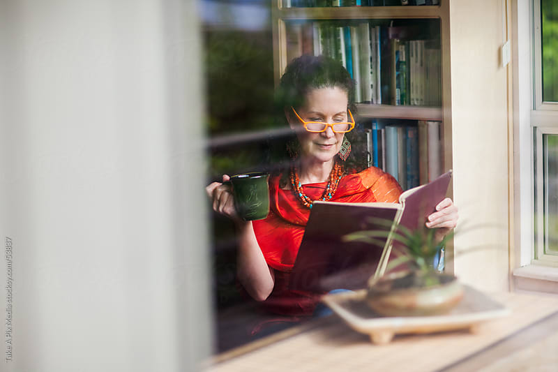Middle age woman reading a book at home while holding a cup of c by Suprijono Suharjoto for Stocksy United