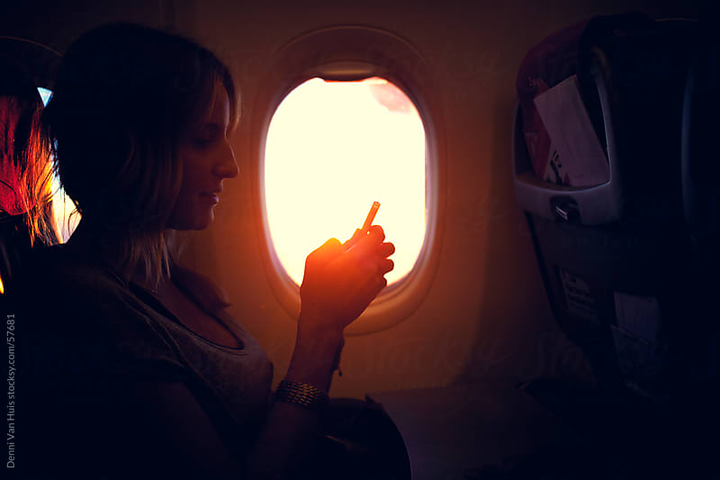 Young woman sitting in an airplane using her phone by Denni Van Huis for Stocksy United