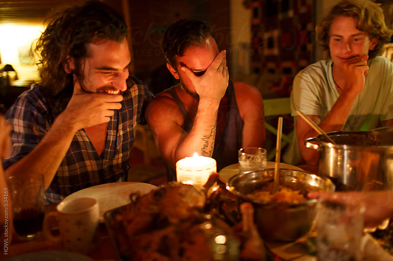 Friends sit around laughing and enjoying a dinner in candlelight by HOWL for Stocksy United