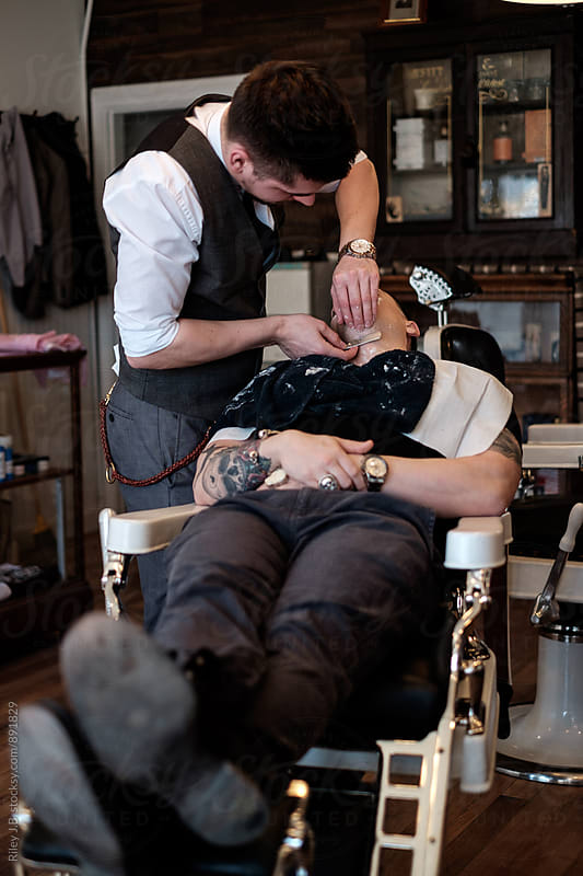 A gentleman barber shaves under the chin of a client with a classic straight razor. by Riley J.B. for Stocksy United