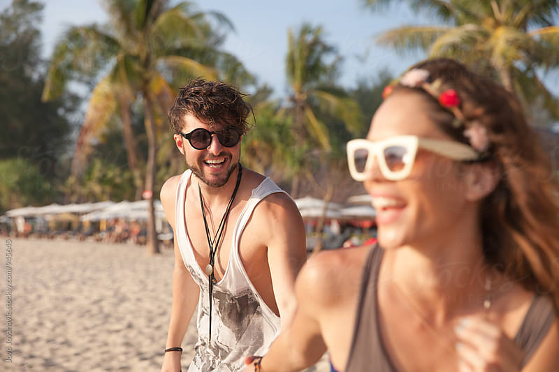 Couple having fun at the beach by Jovo Jovanovic for Stocksy United