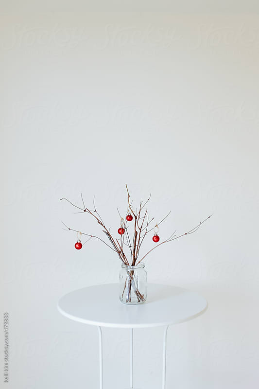 Minimal holiday decor of branches with red ornaments by Kelli Seeger Kim for Stocksy United