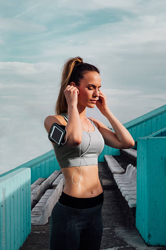Beautiful Sporty Woman Listening Music  by Katarina Radovic for Stocksy United