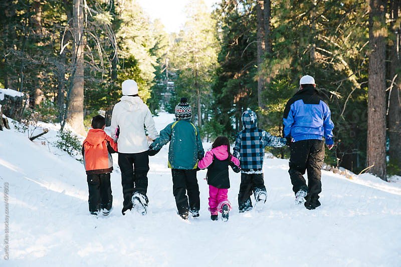 Family walking on snow on a winter's day by Curtis Kim for Stocksy United