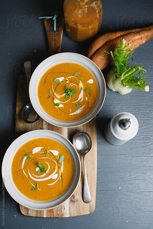 Two bowls of sweet potato and fennel soup on table. Seen from overhead. by Darren Muir for Stocksy United