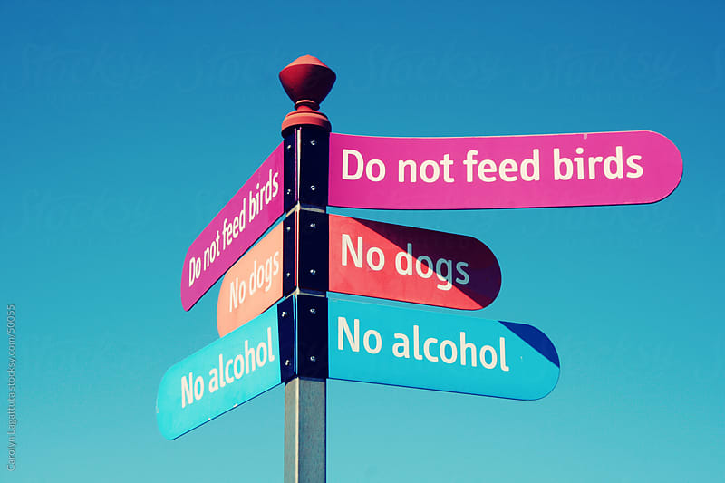 Lots of rules on a sign forbidding people to have dogs or feed birds by Carolyn Lagattuta for Stocksy United
