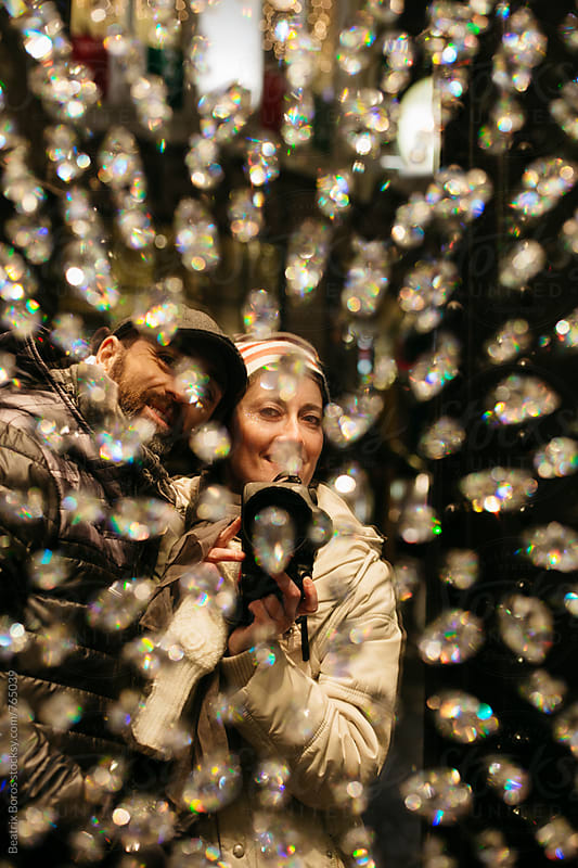Couple taking a selfie of themselves in a shopping window with reflections of Christmas lights by Beatrix Boros for Stocksy United
