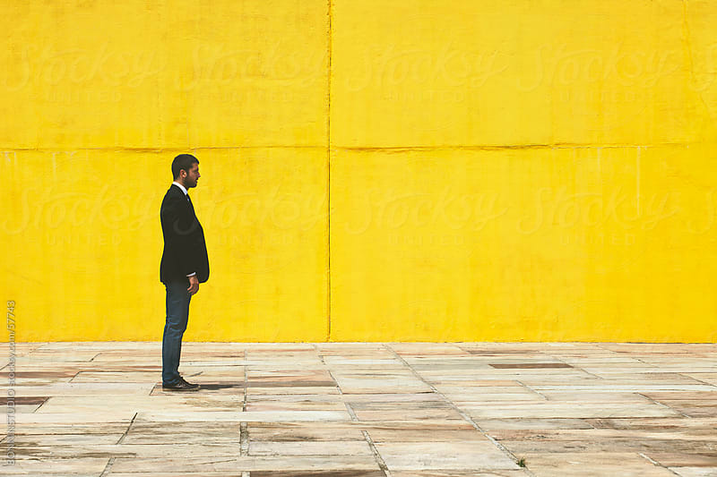 Businessman standing on the street in front a yellow big wall. by BONNINSTUDIO for Stocksy United