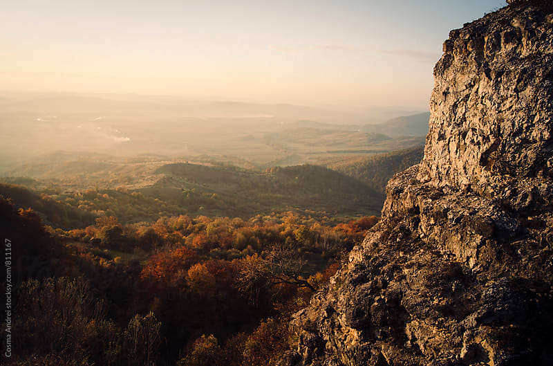 Mountain cliff watching over autumn landscape by Cosma Andrei for Stocksy United