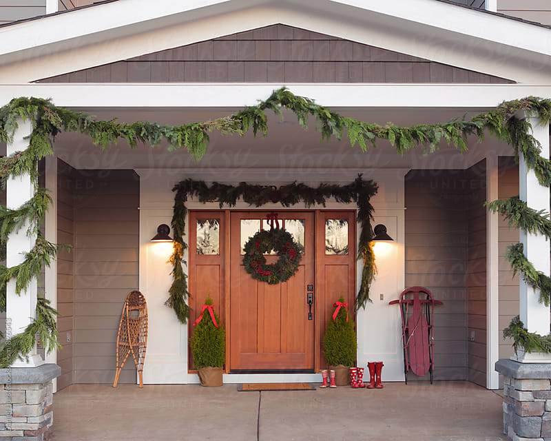 Front door of home decorated for Christmas by Daniel Hurst for Stocksy United