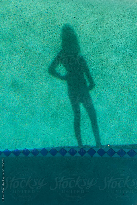 shadow of teen girls over a swimming pool by Gillian Vann for Stocksy United