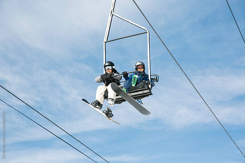 Young snowboarders riding ski lift  by Curtis Kim for Stocksy United