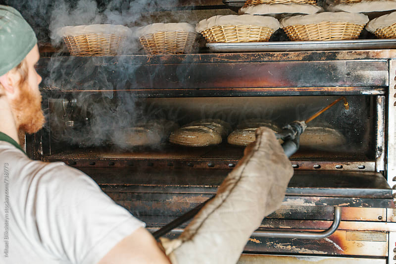 Baker misting bread with water at a commercial artisinal bakery by Mihael Blikshteyn for Stocksy United