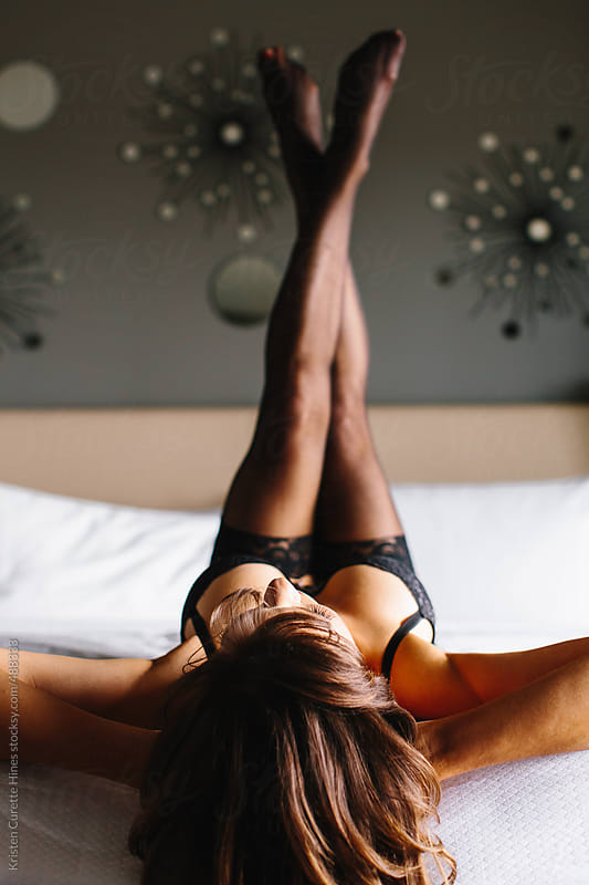 Sexy brunette laying on a bed in boudoir pose  by Kristen Curette Hines for Stocksy United