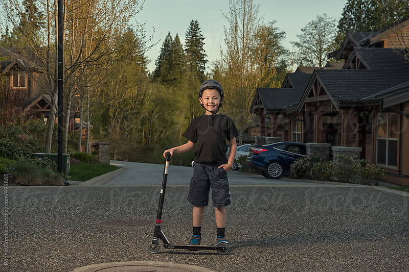 Boy With Scooter by Ronnie Comeau for Stocksy United