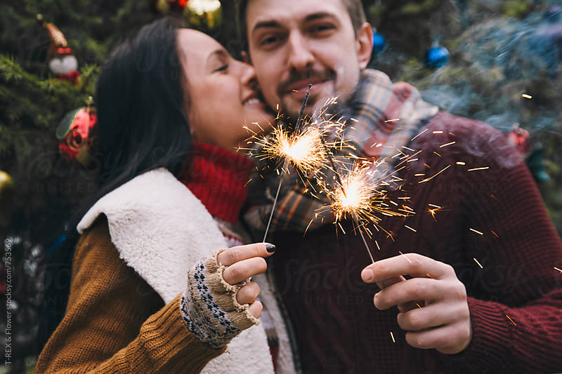 Couple holding Christmas sparklers by Danil Nevsky for Stocksy United