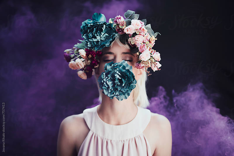 Artistic portrait of a young woman wearing flower crown in a smoke by Jovana Rikalo for Stocksy United