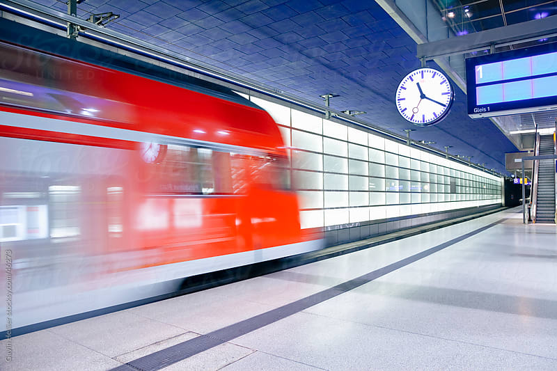 Europe, Germany, Berlin, modern train station  - moving train pulling into the station by Gavin Hellier for Stocksy United