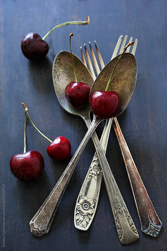 Fresh cherries with old spoons and forks  by Sandra Cunningham for Stocksy United