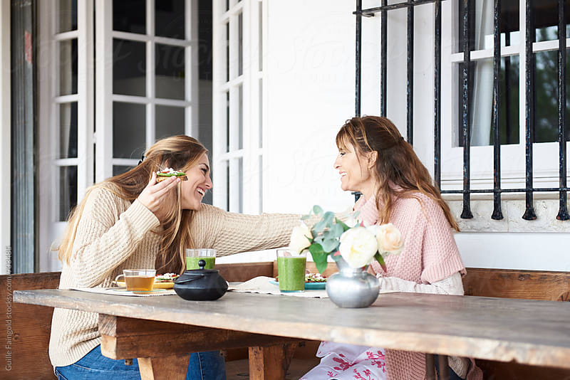Women laughing while having lunch on terrace  by Guille Faingold for Stocksy United
