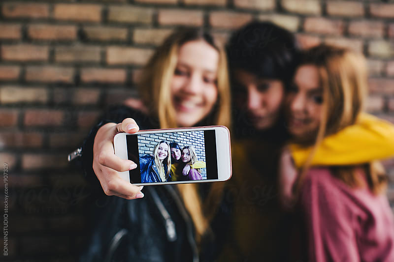 Teen girls taking a selfie with their phone.  by BONNINSTUDIO for Stocksy United