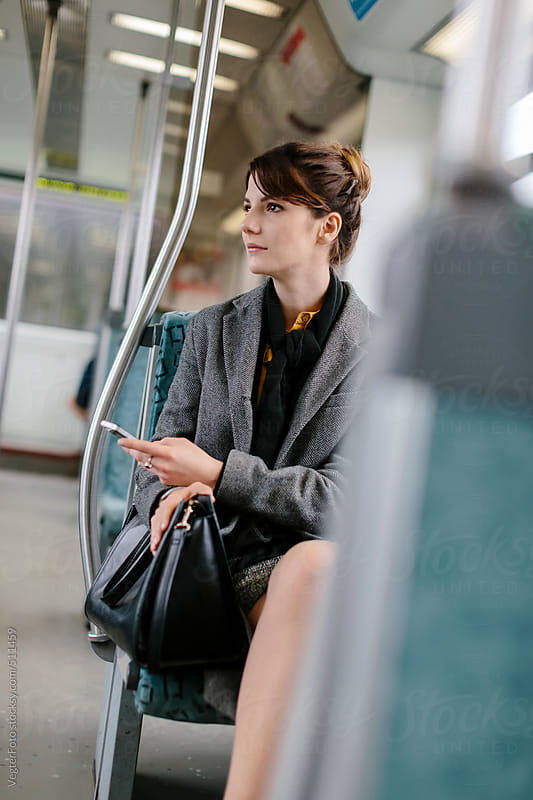 Businesswoman With Smart Phone In Commuter Train by VegterFoto for Stocksy United
