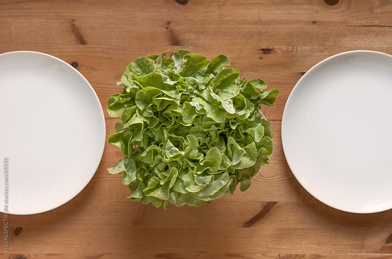 Two White Plates And Lettuce On Wood Table by VISUALSPECTRUM for Stocksy United